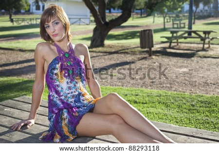 Sexy young girl in a garden with a blue suit