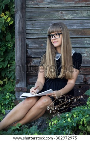 Sexy young girl in a short black dress and sunglasses sitting on the porch of an old house with an album for drawing and pencil - stock photo