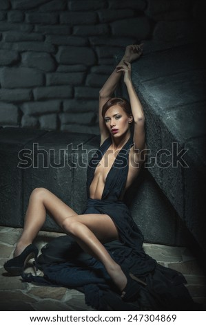 sexy young girl in evening dress  with  hands up. Stone on the background. Fashion photo - stock photo
