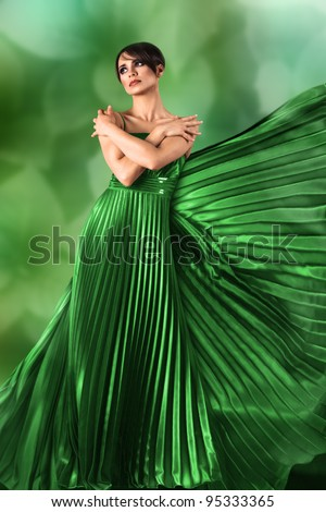 Sexy young girl in long flowing dress against green nature background - stock photo