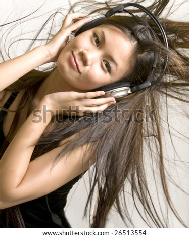 Sexy young girl listening to music on headphones - stock photo