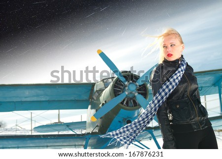 sexy young girl next to the pilot vintage aircraft.Elements of this image furnished by NASA  - stock photo