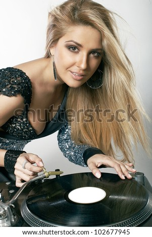 Sexy young girl posing at the professional vinyl record players - stock photo