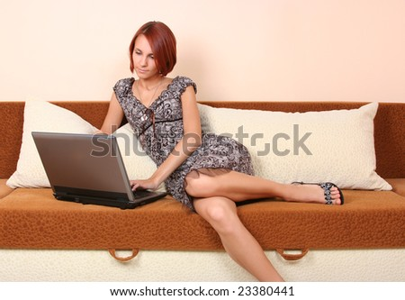 sexy young girl relaxing on sofa with laptop - stock photo