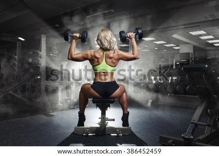 Sexy young girl resting after dumbbells exercises. Fitness woman - stock photo