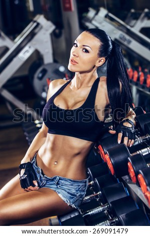 sexy young girl resting after dumbbells exercises. Fitness woman  resting in gym. - stock photo