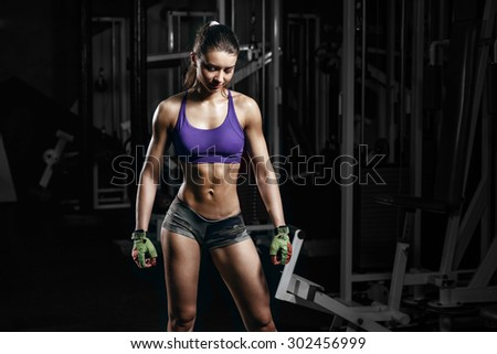 sexy young girl resting after sport workout exercises. Fitness woman in sport wear with perfect fitness body resting in gym - stock photo
