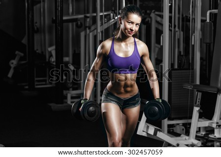 sexy young girl resting doing sport workout exercises with dumbbells. Fitness woman in sport wear with perfect fitness body in gym - stock photo