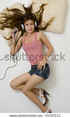 Sexy young girl wearing shorts listening to music on headphones - stock photo