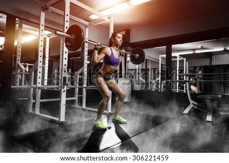 sexy young girl with perfect abs doing squat exercises. Fitness brunette fit woman in gym with barbell - stock photo