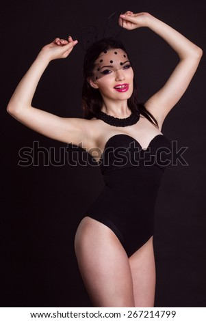 Sexy young girl with slim figure is wearing bunny lace ears mask with veil and fashion makeup  isolated on black - stock photo