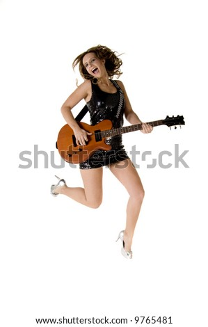 Sexy young glam rock guitarist in a black sequin mini dress and silver high heels jumping in the air with an electric guitar - stock photo