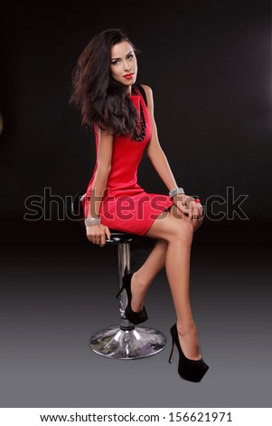 Sexy young gorgeous brunette woman in red dress on the chair, isolated on black, studio shot. - stock photo