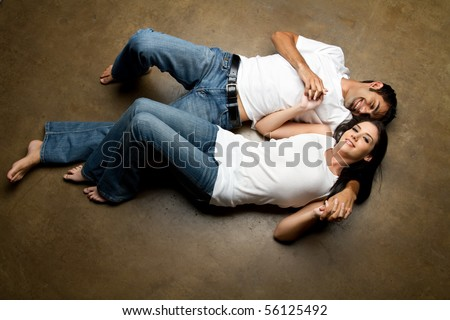 Sexy young happy casual couple relaxing on the floor - stock photo