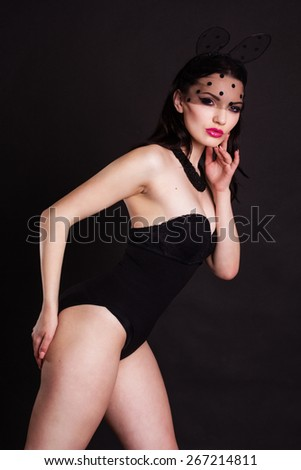 Sexy young lady is wearing bunny lace ears mask with veil and black body isolated on black - stock photo