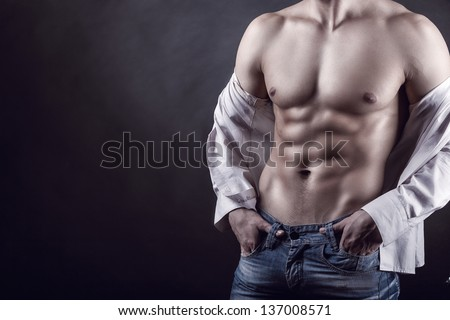 Sexy young man in a shirt with a naked torso on a dark background - stock photo