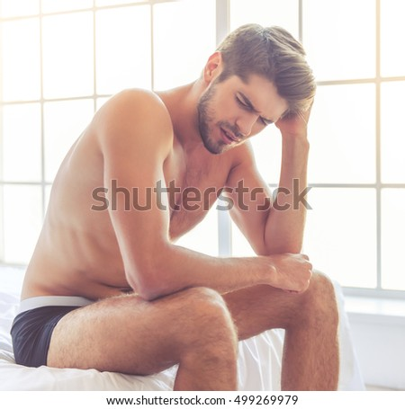Sexy young man in black briefs is leaning on his knees feeling pain while sitting on bed