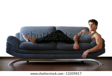 Sexy young man lying on the sofa - stock photo