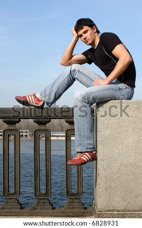 Sexy young man sitting on the embankment - stock photo