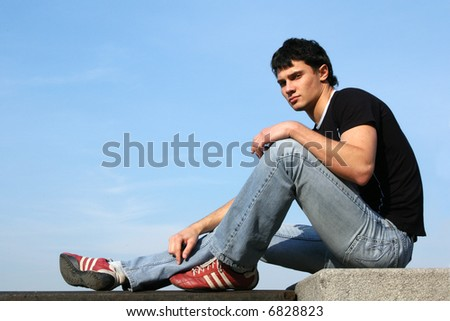 Sexy young man sitting on the stone blocks - stock photo