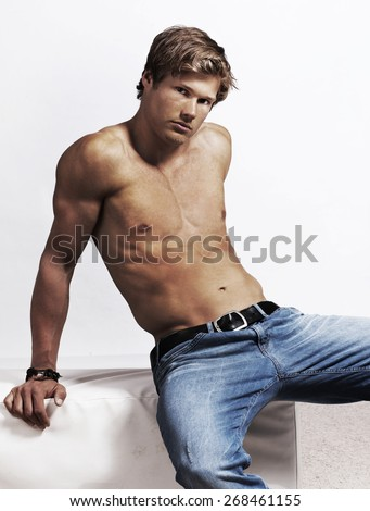 Sexy young man stripped to the waist isolated - stock photo