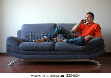 Sexy young man talking on the cell phone sitting on the sofa - stock photo