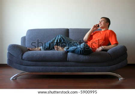Sexy young man talking on the cell phone sitting on the sofa