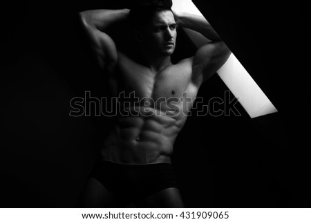 Sexy young man with muscular body and bare torso posing in trunks near window, black and white - stock photo