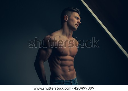 Sexy young man with muscular body and bare torso posing near window - stock photo