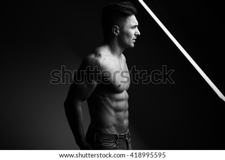 Sexy young man with muscular body and bare torso posing near window, black and white - stock photo