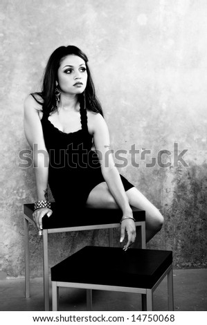 Sexy young multi-ethnic woman in a short black cocktail dress sitting on a side table on a concrete background