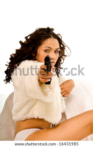 Sexy young multi-ethnic woman wearing white panties and an open white fur shrug sitting with a pistol in her hand - stock photo