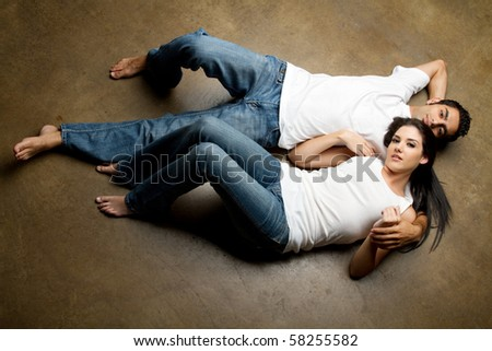 Sexy young multiracial couple in blue jeans relaxing on the floor - stock photo