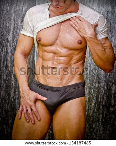 Sexy young muscle man in a shower wearing dark underwear and wet white t-shirt - stock photo