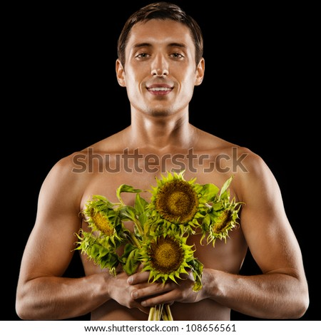 Sexy young muscular man with a bouquet of flowers in his hands. Isolated on black background