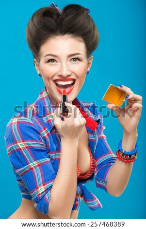 Sexy young pin-up girl doing make-up - stock photo