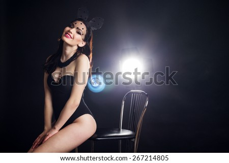 Sexy young pretty lady is wearing bunny lace ears mask with veil and black underwear over studio flash light - stock photo
