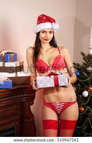 sexy young Santa-girl in red bikini with presents - stock photo