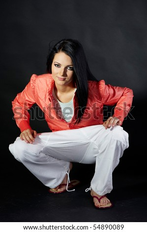 Sexy young slim brunette wearing orange jacket, white ducks and flip-flops (Isolated on the black background)
