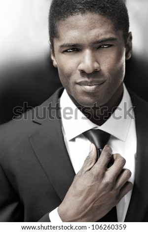 Sexy young stylish businessman in black and white suit - stock photo
