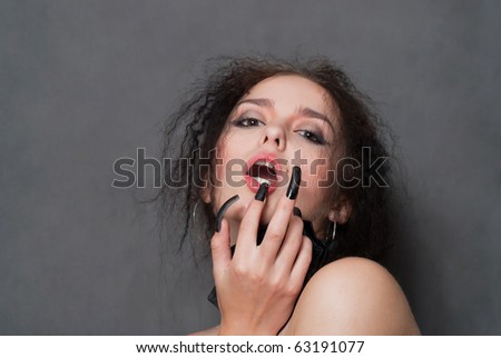 sexy young witch with black nails smiling on gray background