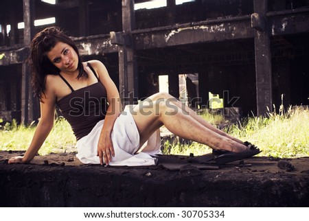 sexy young woman dirty on her legs, with old factory ruins in the background