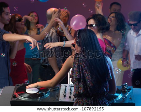 sexy, young woman dj, entertaining the crowd in a night club - stock photo