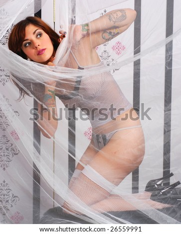 Sexy young woman dressed in black and white lingerie hiding behind sheer curtain - stock photo