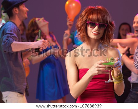 sexy, young woman drinking a cocktail on the dancefloor, in a night club