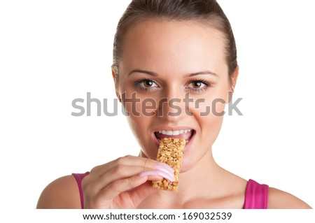 Sexy young woman eating a cereal bar, isolated in white - stock photo