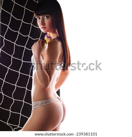 Sexy young woman football fan with perfect body in lingerie standing by net with white copy space  - stock photo