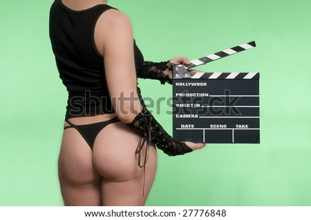 sexy young woman holding a movie clapper against a green screen