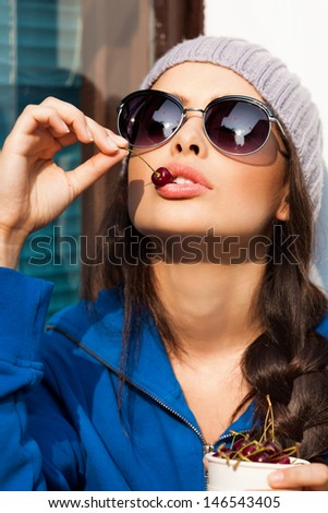 Sexy young woman holding a tasty cherries. Lifestyle, outdoors - stock photo