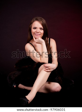 Sexy young woman in a fur coat on dark background.